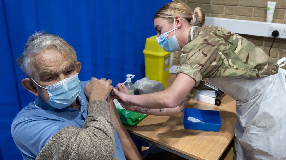 Man being vaccinated by military personnel