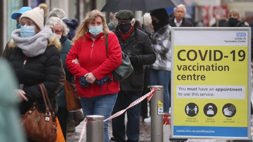 Members of the public queueing at COVID vaccination centre