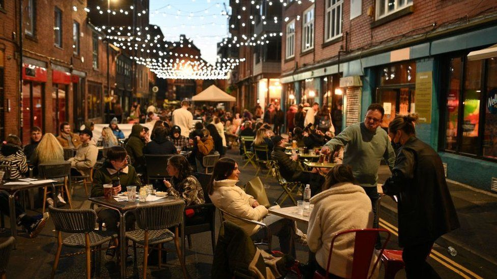 Groups of people sat at tables outside bars in the Northern Quarter of central Manchester