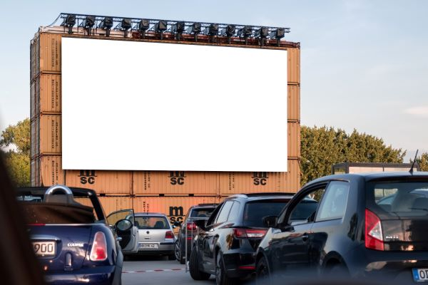 Drive-in cinema screen with cars present