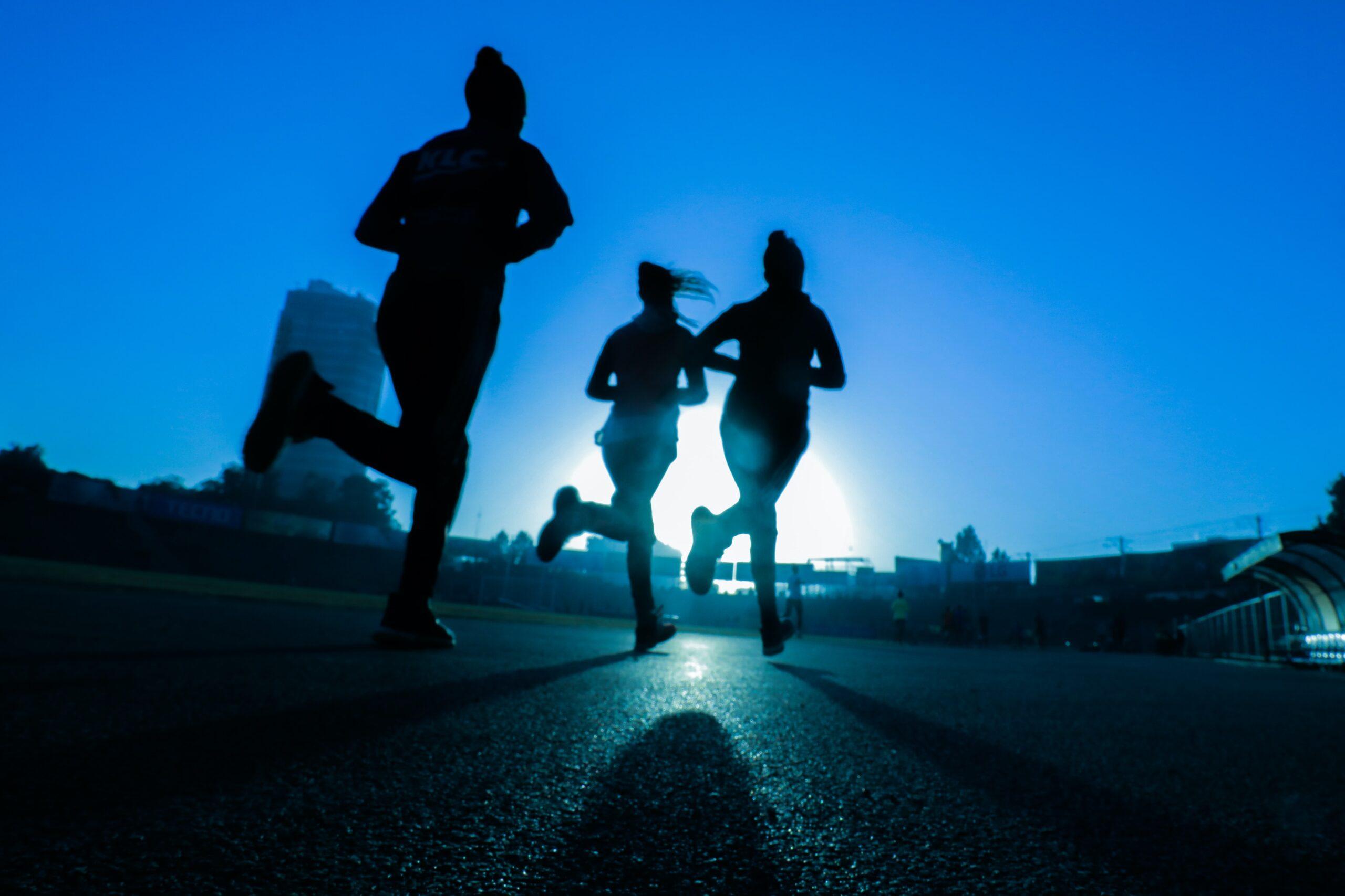 Three joggers running into the sunset