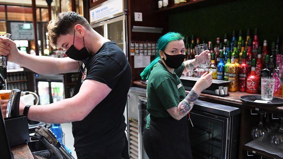 Bar staff preparing drinks whilst wearing masks