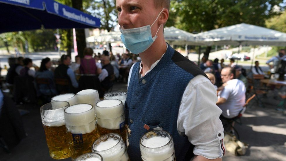 Man carrying various pints of beer at Oktoberfest 2019