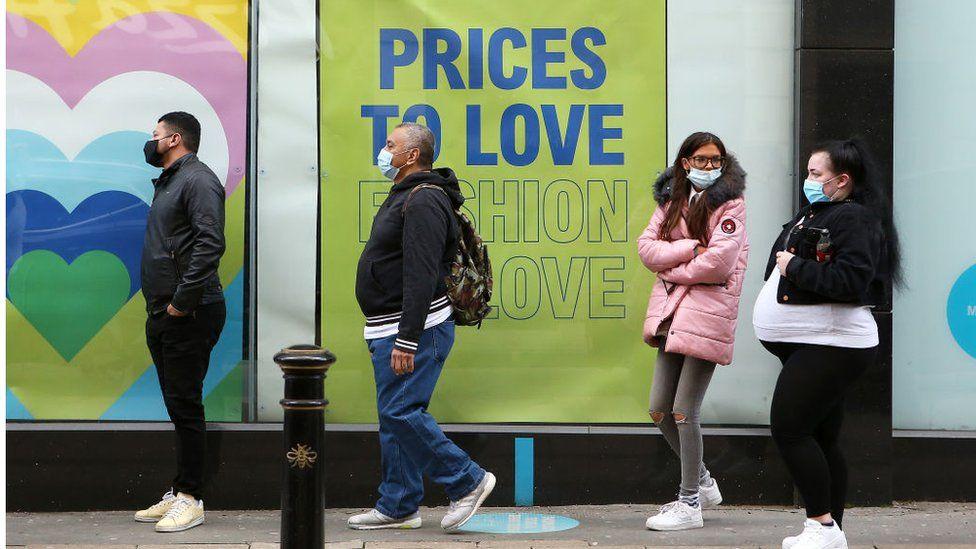 Shop-goers queue outside retail establishment wearing masks, 1m apart