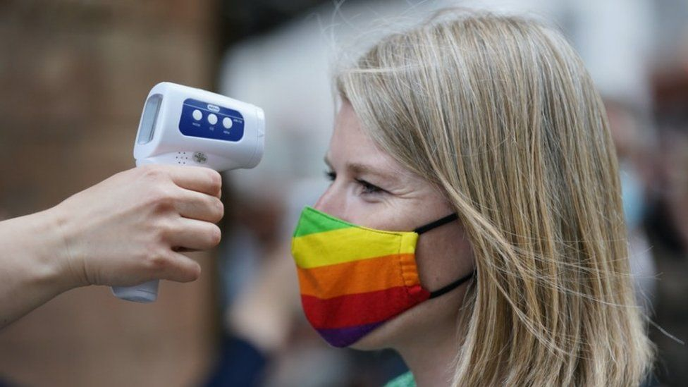 Woman wearing rainbow Pride face mask has her temperature checked for Covid-19