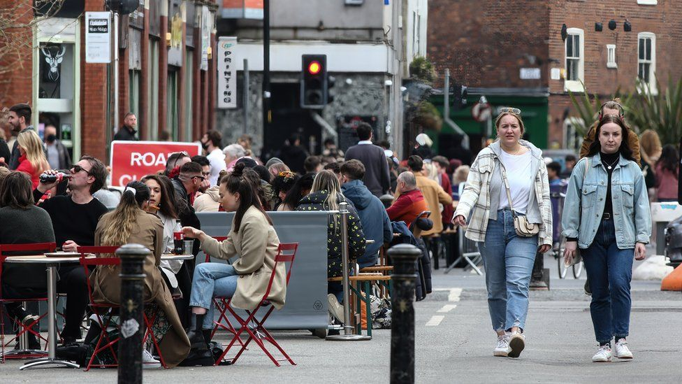 Busy high street with people sat at outside dining and drinking areas