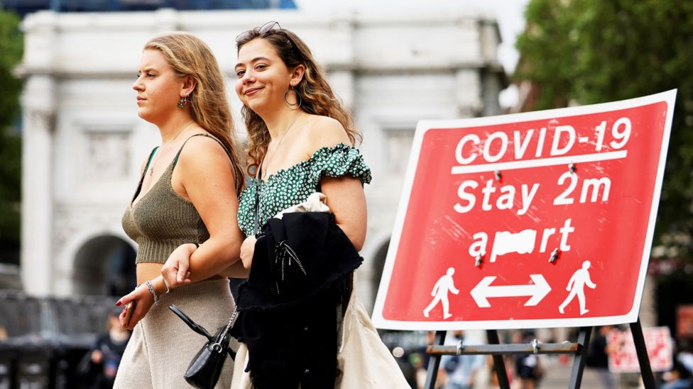"""Two women walk arm-in-arm past a """"COVID-19 Stay 2m apart"""" sign"""