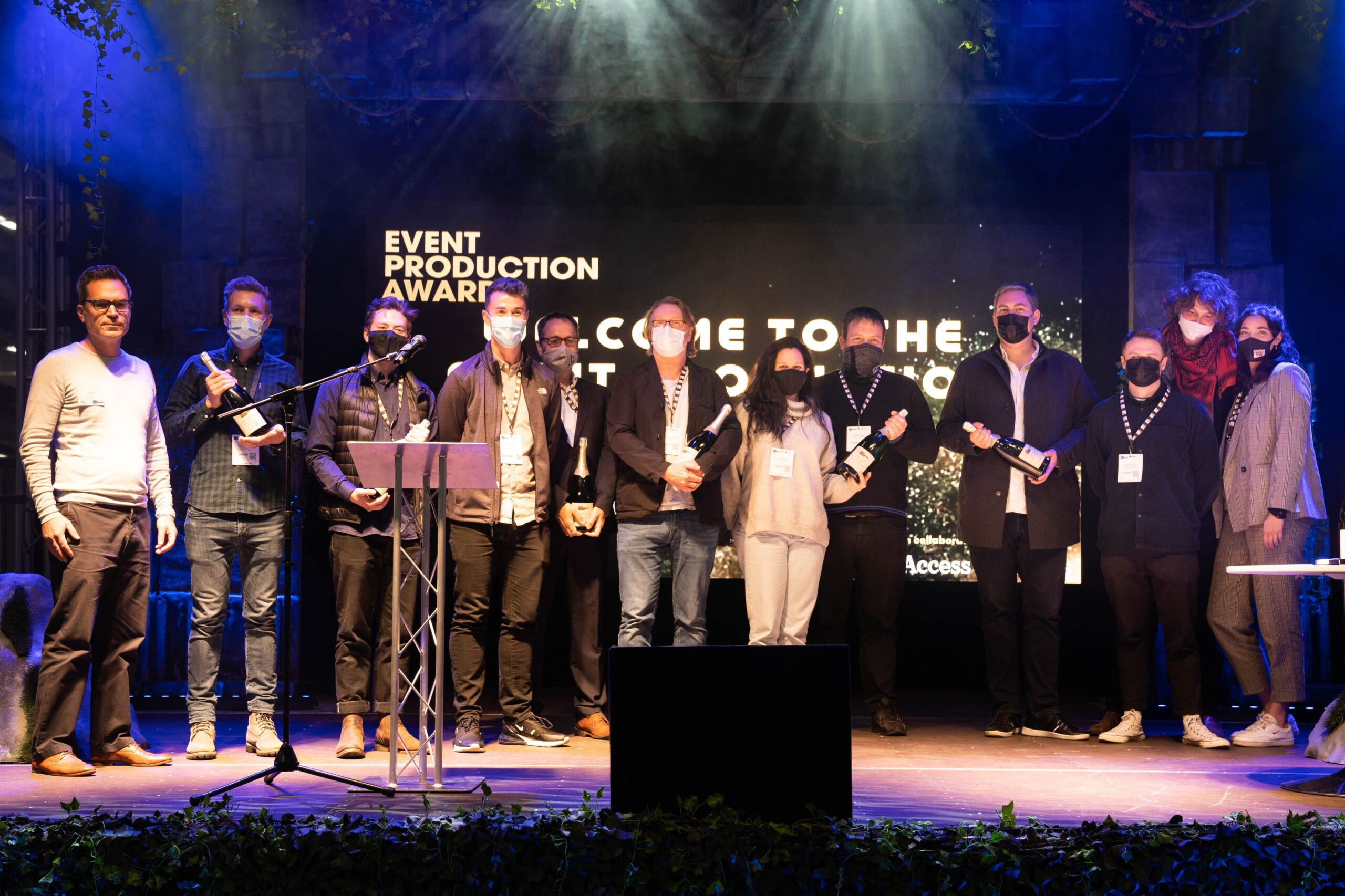 Winners of the EPA's stand on stage each holding a bottle of champagne
